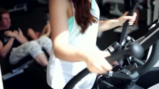 Young Woman Uses Elliptical Cross in a Gym