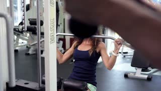 Young Woman Uses Lat Machine (training apparatus)