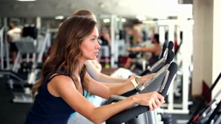 Young Women use Exercise Bicycles in a Gym