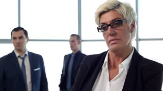 You're Fired/We see frustrated businesswoman, who learned about his dismissal. In the background are her colleagues. The action takes place in the office on the background of large window