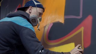 Graffiti artist painting on the wall, interior