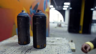 Graffiti artist taking cans of, slow motion, interior