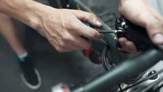 Professional mechanic repairing bike part with tools in workshop