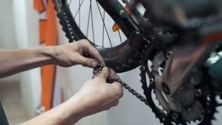 Professional mechanic setting up chain on bicycle with tool in workshop