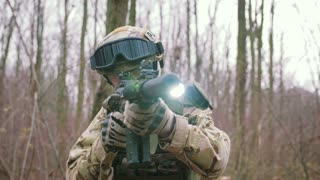 Armed young man in a zone of armed conflict in uniform targeting with assault rifle walking in forest, slow motion. Airsoft