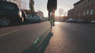Cyclist man riding fixed gear sport bike in sunny day on a city at sunset