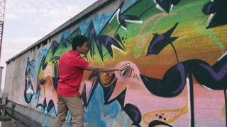 Graffiti artist painting on the wall, exterior