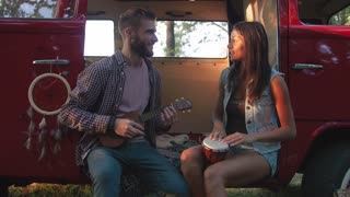 Happy young cheerful couple playing instruments and having some fun in retro hippie minibus in forest