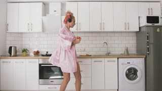 Happy young woman with pink hair dancing in kitchen wearing pink pajamas and listening to music with headphones