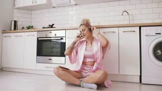 Happy young woman with pink hair sitting on the floor on kitchen wearing pink pajamas and listening to music with headphones