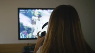 Young attractive woman gamer with headphones playing video game on PC, back view