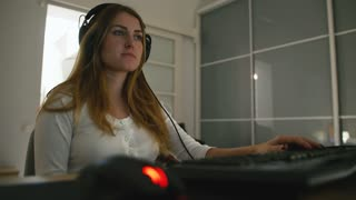 Young attractive woman gamer with headphones playing video game on PC