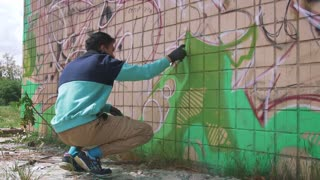 Young man graffiti artist painting on the wall, exterior