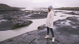 Young woman near the powerful waterfall in Iceland