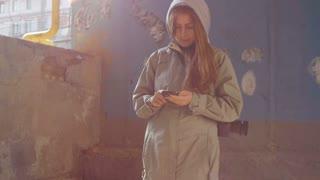 Young attractive female using smartphone in ghetto