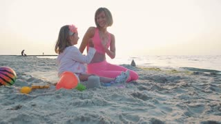 Young mother and her little daughter giving high fives on the beach, slow motion