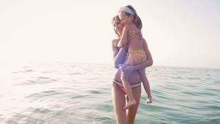 Young mother with her little daugter having fun on the beach near the water