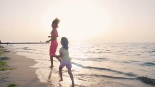 Young mother with her little daugter running on the beach near the water, slow motion