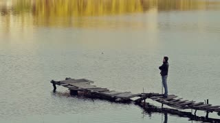 a man stands on the old bridge