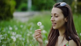 Attractive Girl Blowing on Dandelion