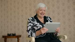 Cheerful Senior Woman connected by Skype