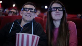 Couple in 3D glasses waching a movie at cinema