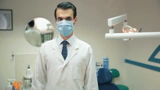 Dentists man take of mask and smiling