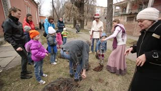 DONETSK, UKRAINE- 06 April 2015: Children with their parents planting trees