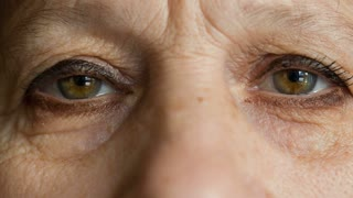 Eyes of elderly women look at camera