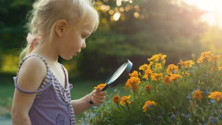 Girl with magnifying glass exploring flowers