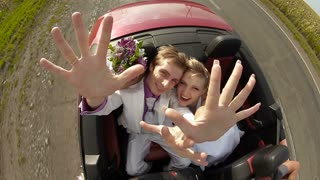Happy newlyweds in a car