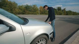 Man and broken car on the road