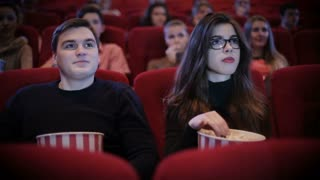 Man holding woman on a date in cinema