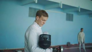 Man puts on fencers mask