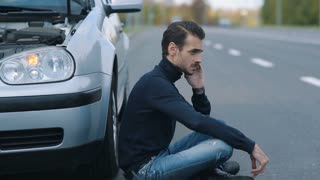 Man siitting near broken car and calling for help