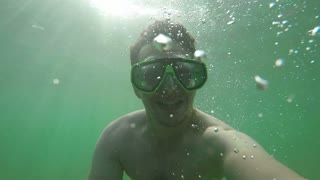 Man Smiling Under Water and Shows Peace Sign