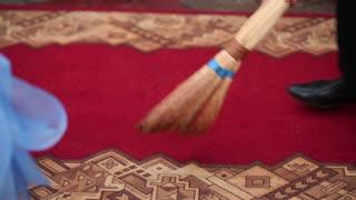 Man Sweeping Red Carpet