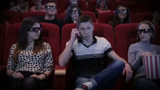 Man talking by phone at cinema
