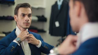 Man tying a tie at boutique