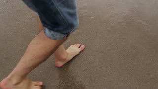 Man's Feet Walking on the Beach