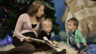 Mother with little children reading a book