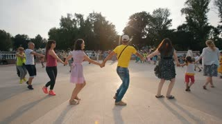 People Dancing in a circle holding hands