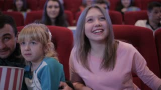 people watching movie in cinema and laughing