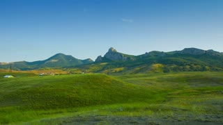 Scenic View of the Mountains and Green Meadow