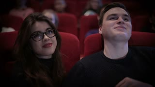 Smiling Couple waching a movie at cinema