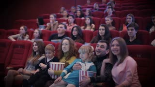 Smiling people watching movie in cinema