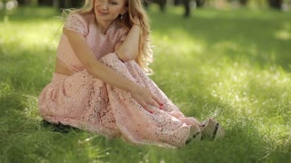 Smiling Romantic Woman Sitting On The Grass