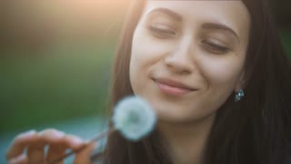 Smiling Woman Blowing on a Dandelion