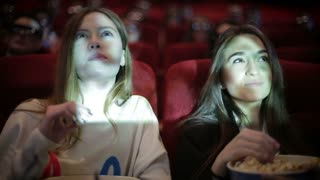 two friends watching movie in cinema
