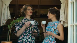 Two Old fashioned woman drink tea and talking